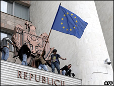 Moldovans wave a European Union flag from atop the entranceway to the parliament building in Chisinau  (7 April 2009)