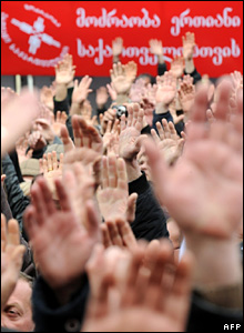 Opposition protesters raise their hands at the demonstration in Tbilisi