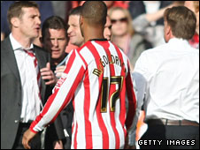 Phil Parkinson (far left) is restrained during a touchline confrontation with Mark Wotte (far right)