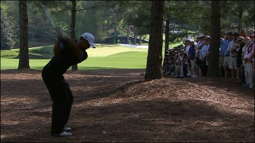 Tiger Woods hits out of the trees on 11th