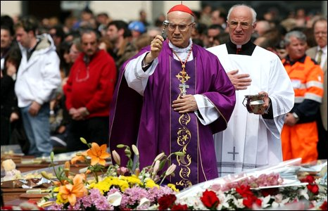 Cardinal Tarcisio Bertone blesses the coffins of victims at the funeral mass in L'Aquila, Italy, 10 April 2009