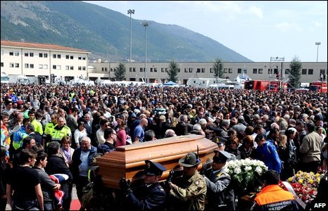 Volunteers, rescuers and soldiers carry a coffin at the end of the funeral in L'Aquila, 10 April 2009.
