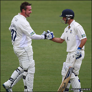 Ian Blackwell is congratulated on his century by captain Will Smith (right)