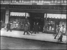 Black and white photo of an old woolworths store with people walking in front on the pavement