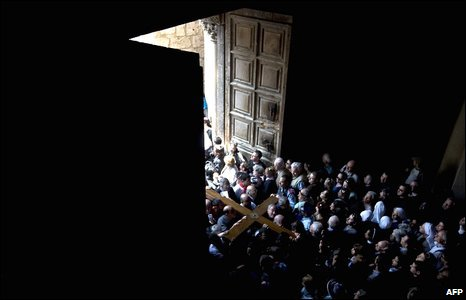 Christian pilgrims carry a cross into Jerusalem's Church of the Holy Sepulchre