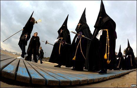 Penitents take part in the Christ the Saviour brotherhood procession of the Holy Week at the beach in Valencia, Spain