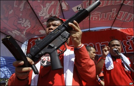Protesters and supporters of exiled Prime Minister Thaksin Shinawatra display a gun, Bangkok 12 April