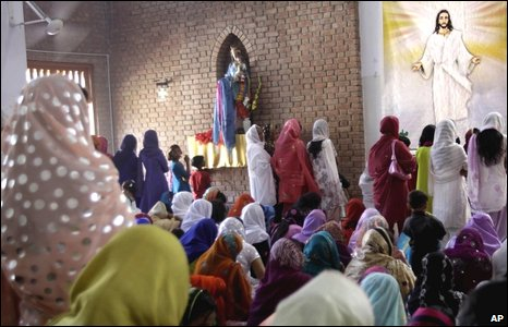 Pakistani Christians pray next to a poster of Jesus Christ during Easter Mass at a Catholic church in Peshawar, Pakistan