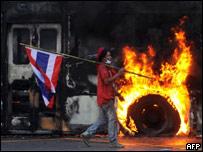 Демонстрант с таиландским флагом на фоне горящего автобуса