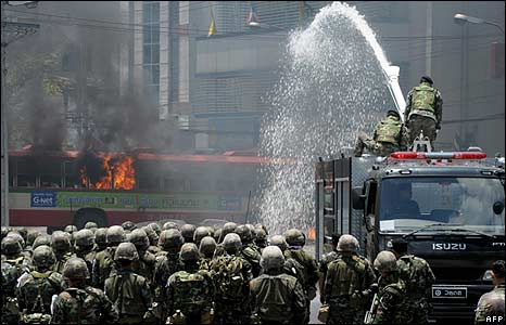 Soldiers use water cannon to douse flames on bus in Bangkok on 13/4/09