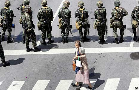 Two elderly women walk past troops in Bangkok on 13/4/09