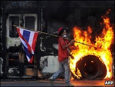 A protester walks past a burning bus in Bangkok, 13 April 2009