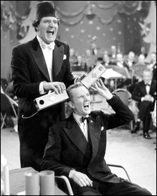 Tommy Cooper plays tricks on BBC announcer McDonald Hobley at a televised Christmas party in 1952.