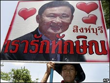 A protester holds a sign praising former Thai leader Thaksin Shinawatra