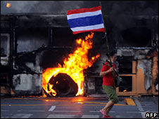 A protester carries a Thai flag as a bus burns in Bangkok on 13 April 2009