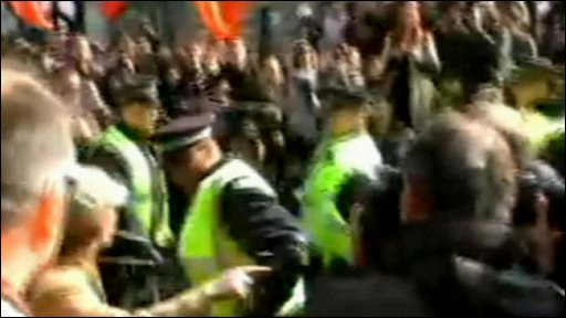 Still from YouTube video of police officer hitting female protester