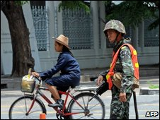 A cyclist rides past a soldier standing guard on a street near to the government office in Bangkok on April 15, 2009.