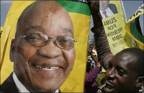 A man holding up a poster of a smiling Jacob Zuma