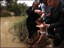 A Christian Orthodox priest baptises a baby in the Jordan River