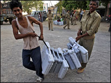 Men carry electronic voting machines in the Indian state of Bihar on 15 April 2009