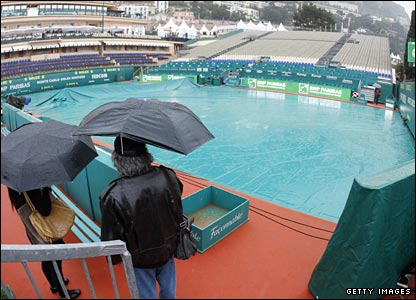 Fans shelter under umbrellas at the Monte Carlo Masters