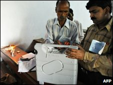 Election officials pack and seal Electronic Voting Machines following the end of voting at a polling both in Varanasi