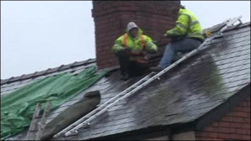 Two men repair the slates on a roof