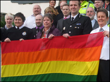North Wales police officers hold the rainbow flag