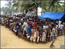 Sri Lankan ethnic Tamil children wait in a queue to receive food at a camp for internally displaced people in a war zone area, Sri Lanka, 12 April 2009