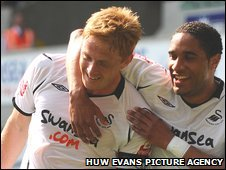 Swansea captain Gary Monk is congratulated by defensive partner Ashley Williams