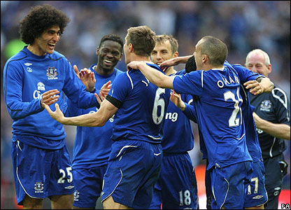 Phil Jagielka is mobbed by his delighted Everton team-mates