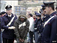 Italian police escort one of the migrants on arrival in Porto Empedocle (20 April 2009)