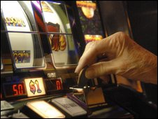 A player puts a coin in an Atlantic City slot machines