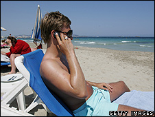 Tourist using mobile phone on beach in Ibiza