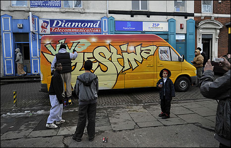 People looking at graffiti covered van