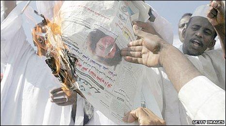 Sudanese demonstrators burn a newspaper bearing the photo of Gillian Gibbons