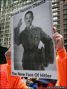 "A Tea Party tax protester holds up a banner which reads ""Barack Hussein Obama - The New Face of Hitler"""