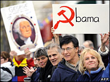 Tea Party tax protestors hold up a banner with the word Obama on it, in which the letter 'O' has been replaced by a hammer and sickle