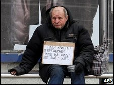 A homeless Russian man sits under a billboard in Moscow on 7 April, 2009