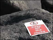 Keep off the rocks sign on rock face