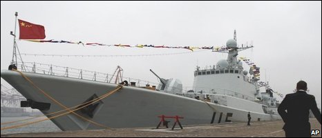 A naval officer runs past Chinese Navy missile destroyer 115 Shenyang docked at Qingdao port