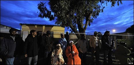 Voters queue in Khayelitsha township on the outskirts of Cape Town as dusk falls on Wednesday