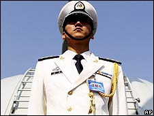 A Chinese navy soldier guards a warship at Qingdao port