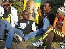 ANC supporters relax by a poster of Jacob Zuma on election day in Johannesburg