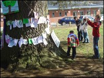 Children hanging banners on the tree