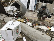 A US soldier inspects debris after a suicide bomb exploded while food aid was being distributed in Baghdad, 23 April 2009