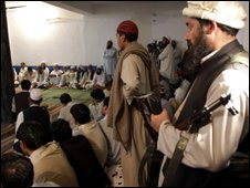 A Taliban militant holds his weapon inside the mosque where tribal elders and the Taliban met in Daggar, Buner's main town