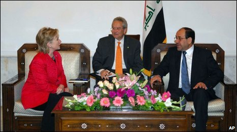 Hillary Clinton, left, speaks with Nouri al Maliki, right, in Baghdad with the help of a translator (centre)