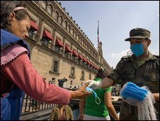 A soldier hands out masks outside the National Palace in Mexico City on Saturday