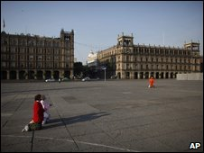 Women in surgical maskas pray in the empty Zocalo plaza in Mexico City, 26 April